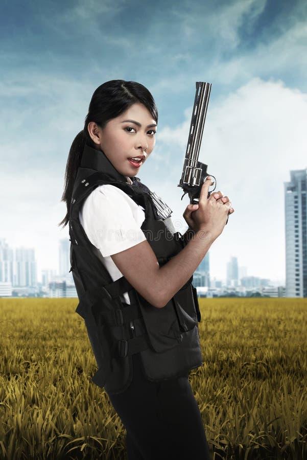 Mujer hermosa de la policía que sostiene el arma fotografía de archivo libre de regalías