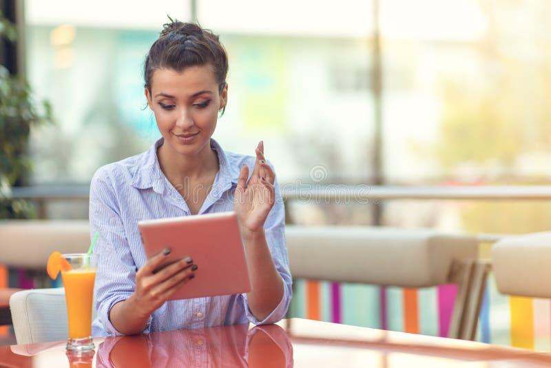 Mujer hermosa de la raza mixta con un peinado afro que celebra una tableta digital en la cafetería foto de archivo libre de regalías