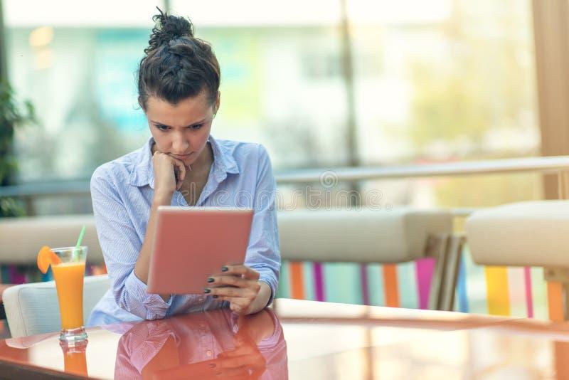 Mujer hermosa de la raza mixta con un peinado afro que celebra una tableta digital en la cafetería imagen de archivo libre de regalías