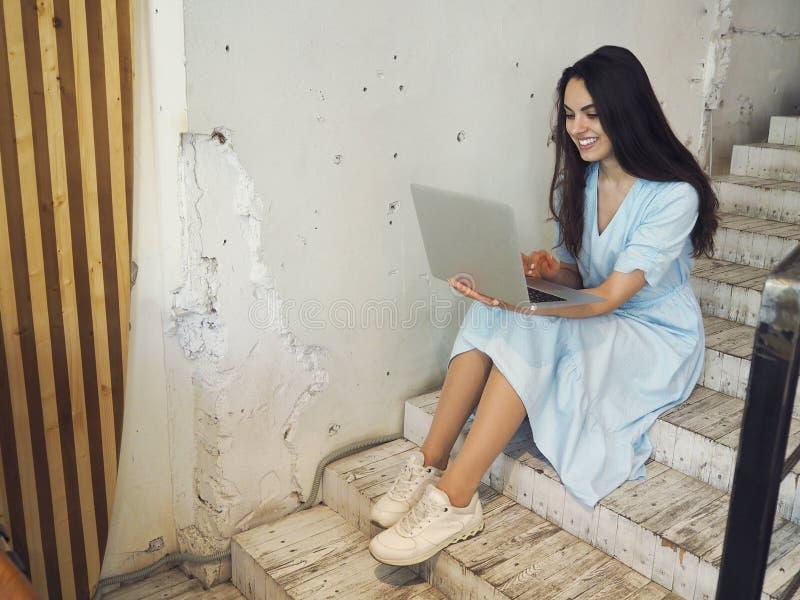 Mujer hermosa de la raza mixta que se sienta en una cafeter?a usando su ordenador port?til fotografía de archivo libre de regalías
