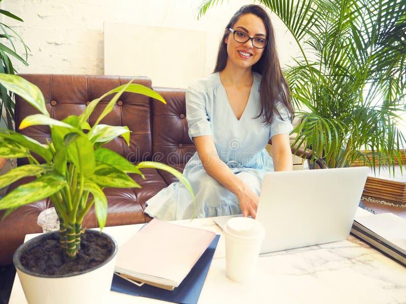 Mujer hermosa de la raza mixta que se sienta en una cafeter?a usando su ordenador port?til foto de archivo