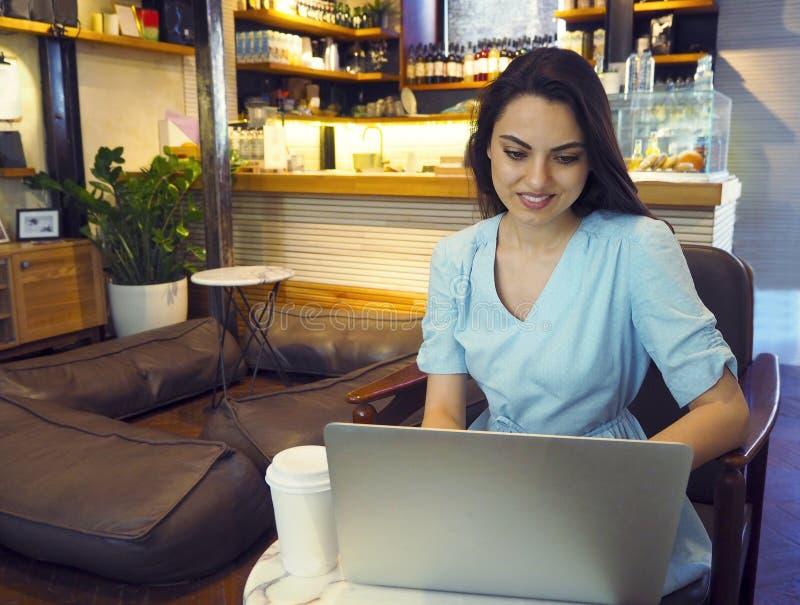 Mujer hermosa de la raza mixta que se sienta en una cafeter?a usando su ordenador port?til fotos de archivo