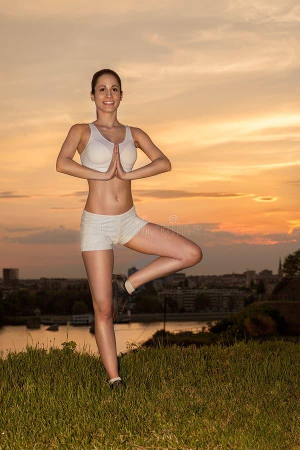 Mujer hermosa de la yoga por la mañana o la puesta del sol imagenes de archivo