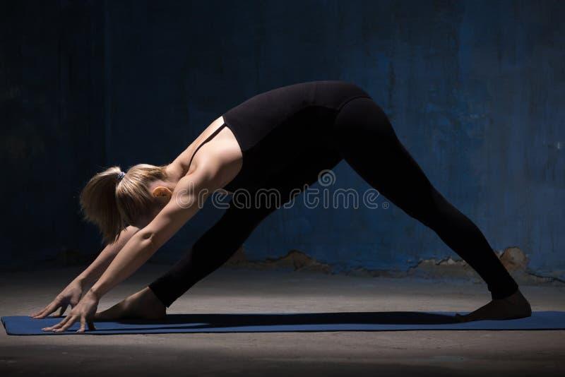 Mujer hermosa de la yoga que hace actitud lateral intensa del estiramiento fotos de archivo libres de regalías