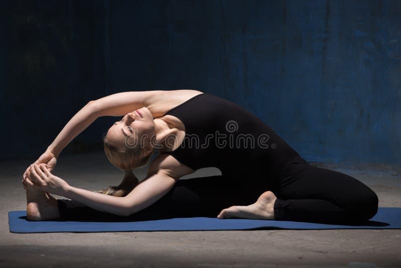 Mujer hermosa de la yoga que se sienta en Parivrrta Janu Sirsasana imagenes de archivo
