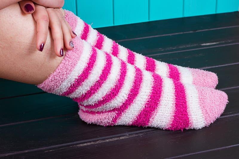 Mujer hermosa de las piernas con la colocación de los calcetines imagenes de archivo