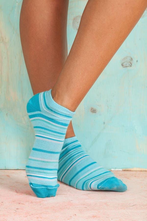 Mujer hermosa de las piernas con los calcetines que se colocan de puntillas en el piso de madera fotos de archivo libres de regalías