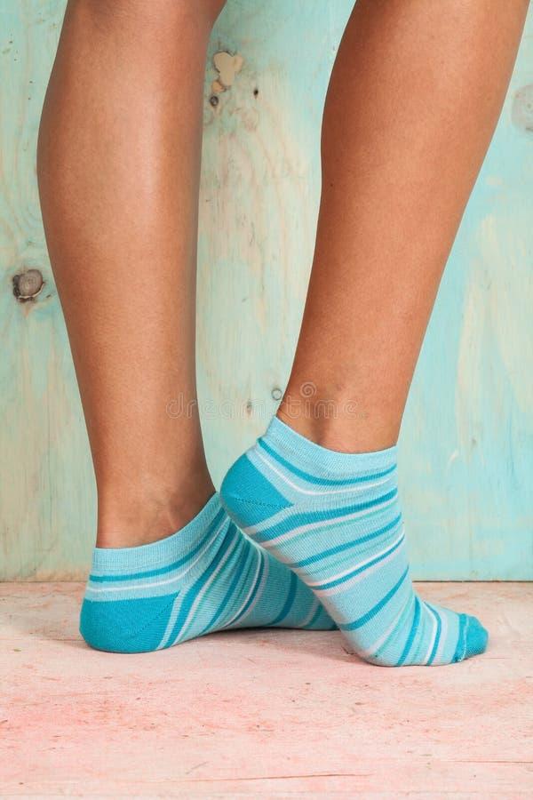Mujer hermosa de las piernas con los calcetines que se colocan de puntillas en el piso de madera imágenes de archivo libres de regalías