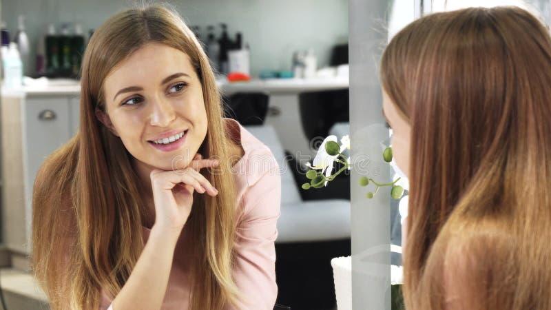 Mujer hermosa de pelo largo joven que mira en el espejo el salón de belleza imágenes de archivo libres de regalías