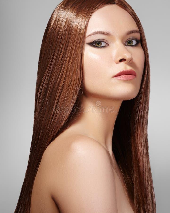 Mujer hermosa de Yong con el pelo marrón de largo recto Modelo de moda atractivo con el peinado liso del lustre Belleza con maqui foto de archivo