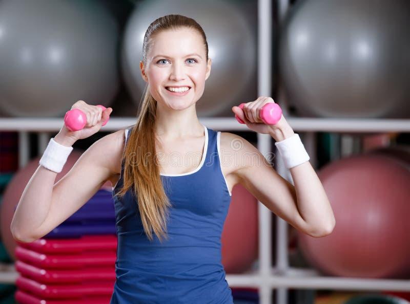 Mujer hermosa del atleta que se resuelve con pesas de gimnasia fotografía de archivo