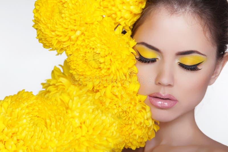 Mujer hermosa del balneario sobre las flores del crisantemo. Observa maquillaje. Bea fotos de archivo libres de regalías