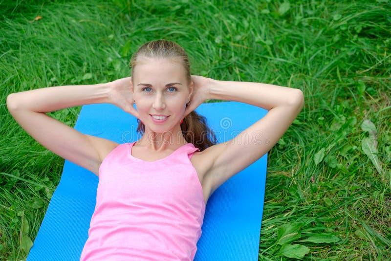 Mujer hermosa del deporte que hace estirando ejercicio de la aptitud en parque de la ciudad en la hierba verde Posturas de la yog fotos de archivo