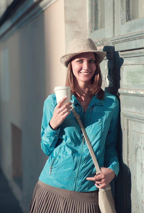 Mujer hermosa del inconformista en sombrero y chaqueta azul con la taza de coffe imagen de archivo libre de regalías