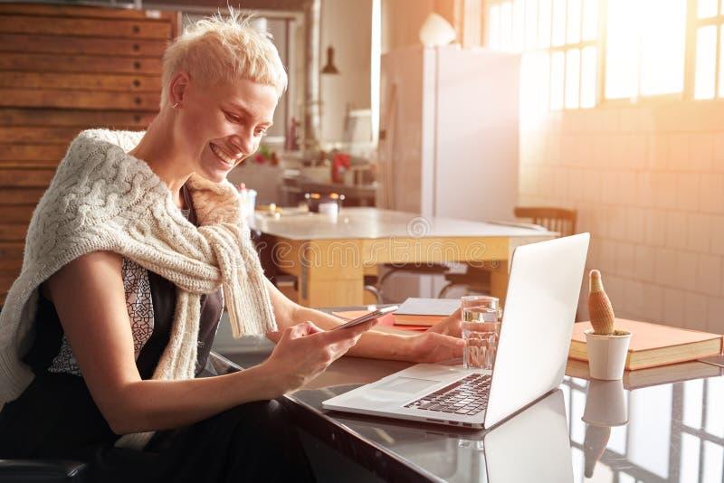 Mujer hermosa del inconformista joven con el pelo corto rubio que sonríe y que usa smartphone móvil, trabajando en el ordenador p imagenes de archivo