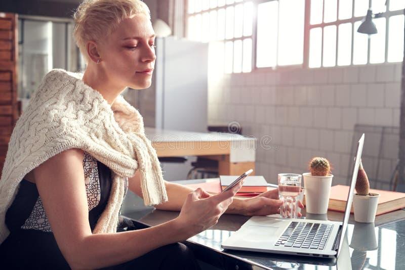 Mujer hermosa del inconformista joven con el pelo corto rubio que sonríe y que usa smartphone móvil, trabajando en el ordenador p imagen de archivo