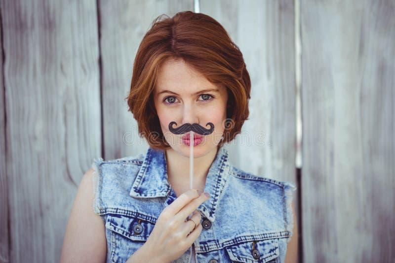 mujer hermosa del inconformista que sostiene un bigote falso imagenes de archivo