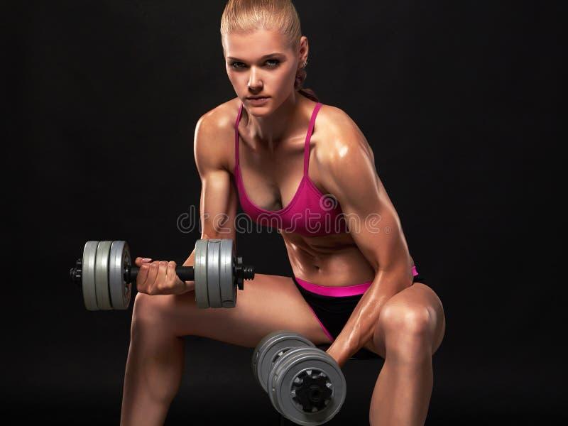 Mujer hermosa del levantamiento de pesas con los músculos imagen de archivo