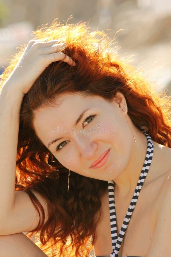 Mujer hermosa del pelirrojo que sonríe y que lleva a cabo sus manos en su pelo foto de archivo