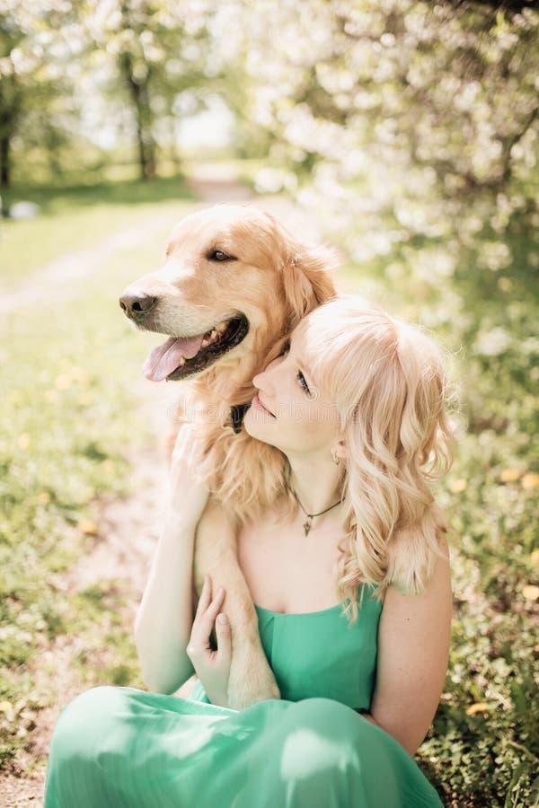 Mujer hermosa del retrato con sentarse lindo del perro del golden retriever fotos de archivo