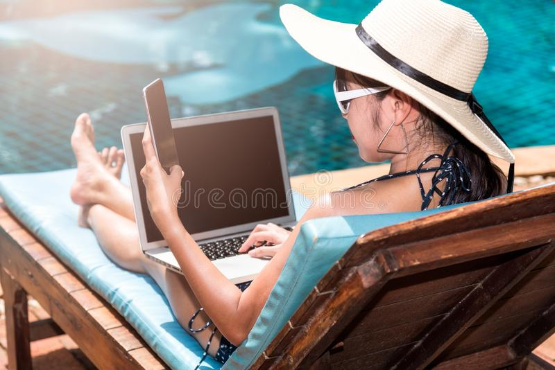 Mujer hermosa del retrato que se sienta en silla de cubierta y que usa el ordenador portátil fotos de archivo libres de regalías