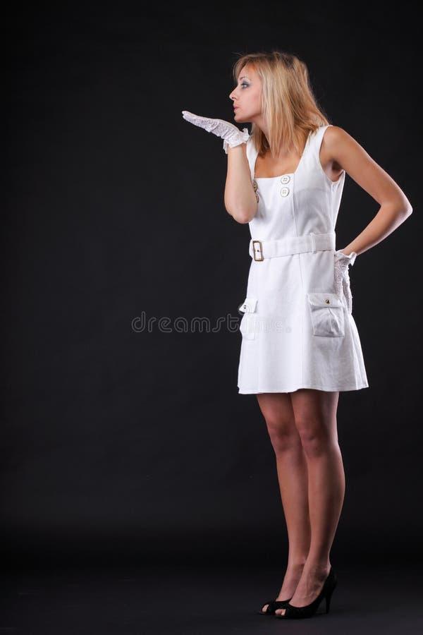 Mujer hermosa del retrato que sopla en los guantes blancos foto de archivo libre de regalías