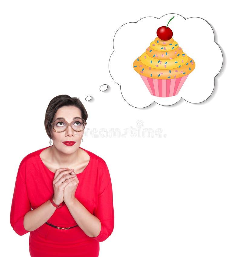 Mujer hermosa del tamaño extra grande en vestido rojo que sueña sobre la torta foto de archivo libre de regalías