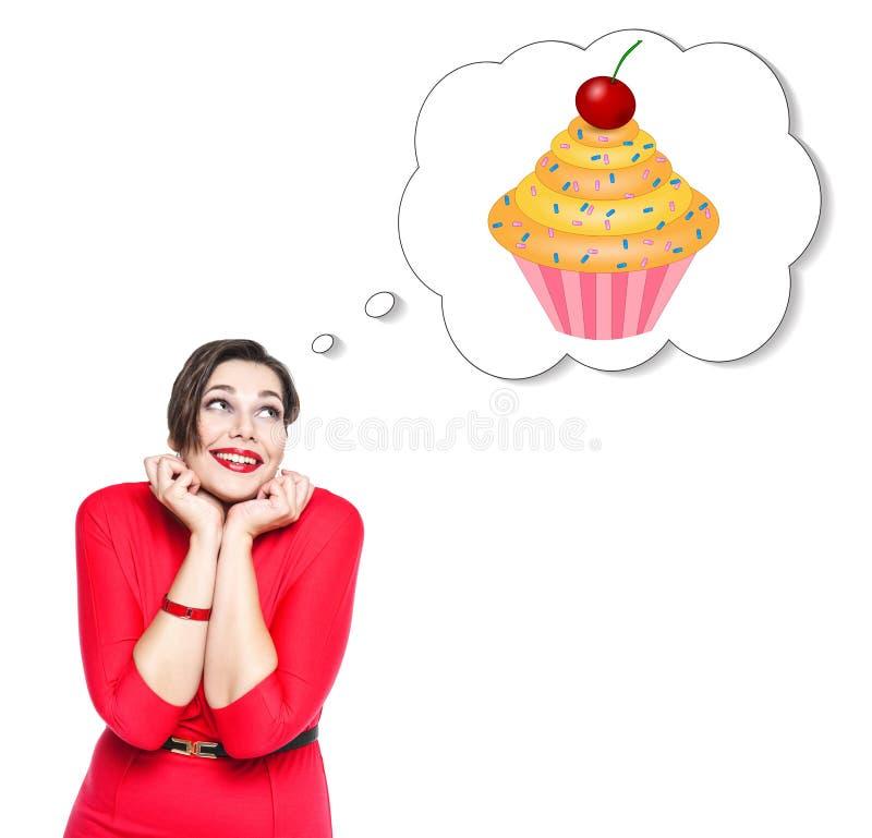 Mujer hermosa del tamaño extra grande en vestido rojo que sueña sobre la torta fotos de archivo