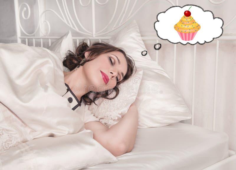 Mujer hermosa del tamaño extra grande que duerme y que sueña sobre la torta fotografía de archivo