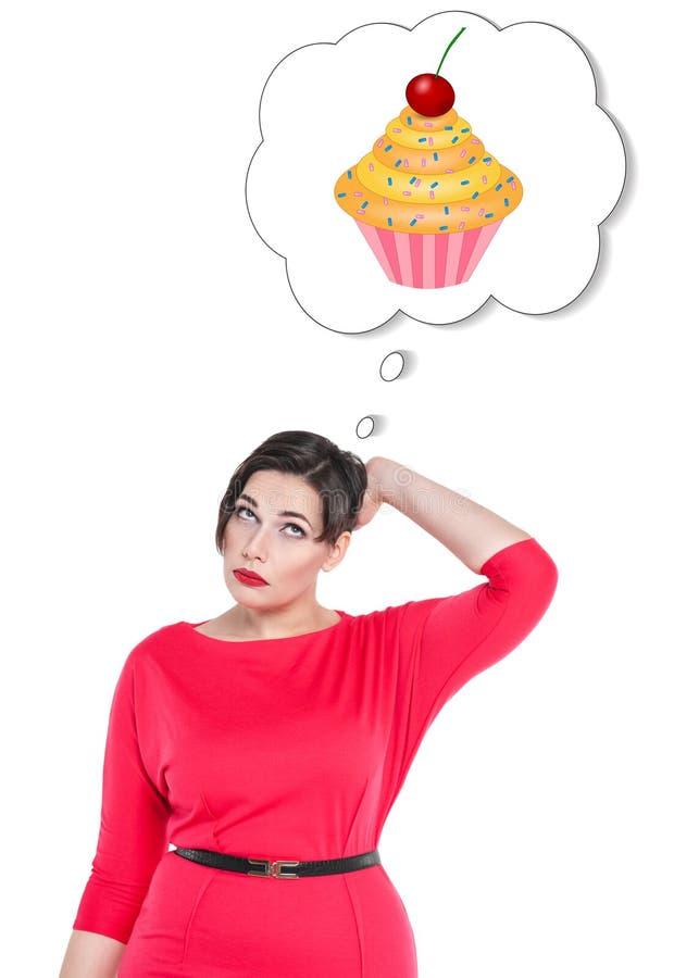 Mujer hermosa del tamaño extra grande que piensa en la torta fotos de archivo
