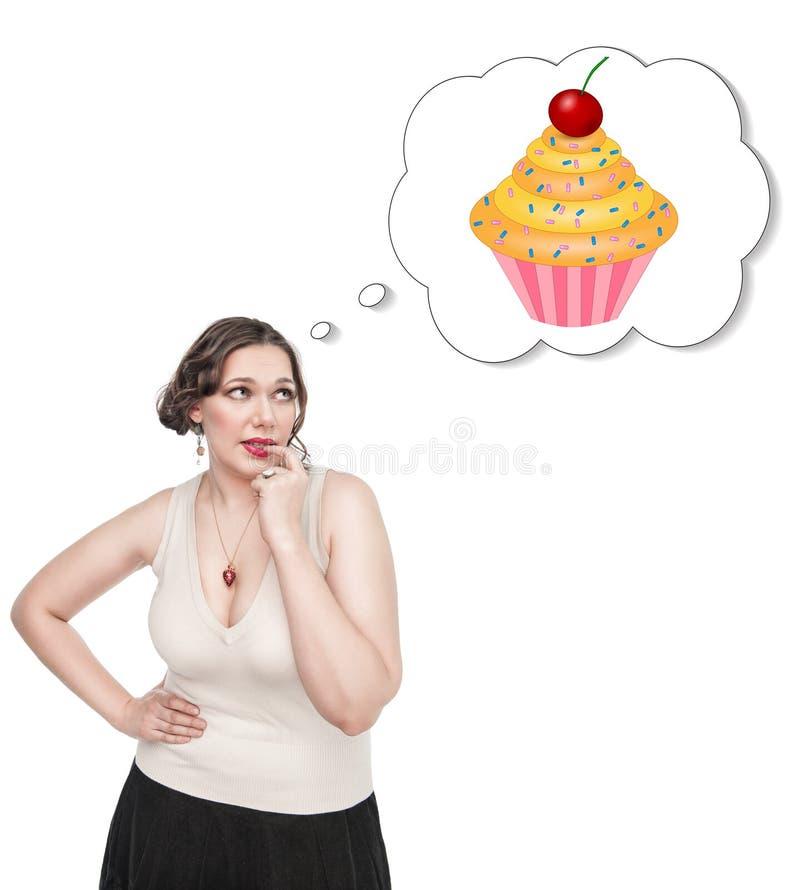 Mujer hermosa del tamaño extra grande que sueña sobre la torta fotos de archivo libres de regalías