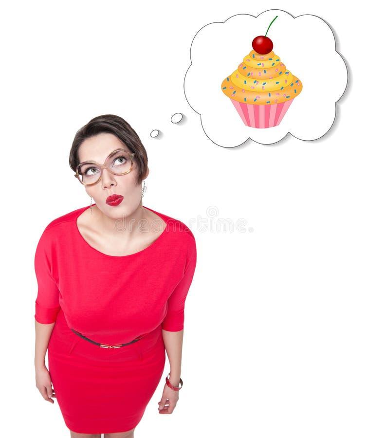 Mujer hermosa del tamaño extra grande que sueña sobre la torta imagen de archivo