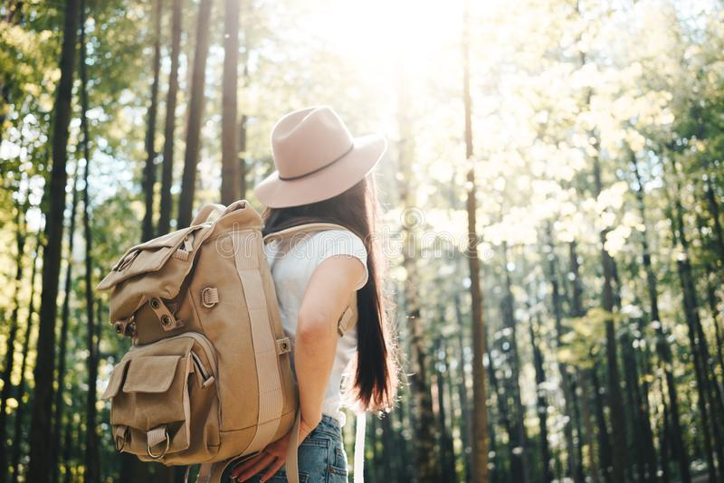 Mujer hermosa del viajero con la mochila y el sombrero que se colocan en la muchacha joven del inconformista del bosque que camin fotos de archivo