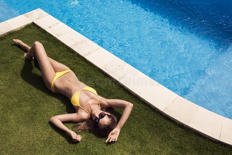Mujer hermosa delgada joven en tomar el sol amarillo del bikini foto de archivo