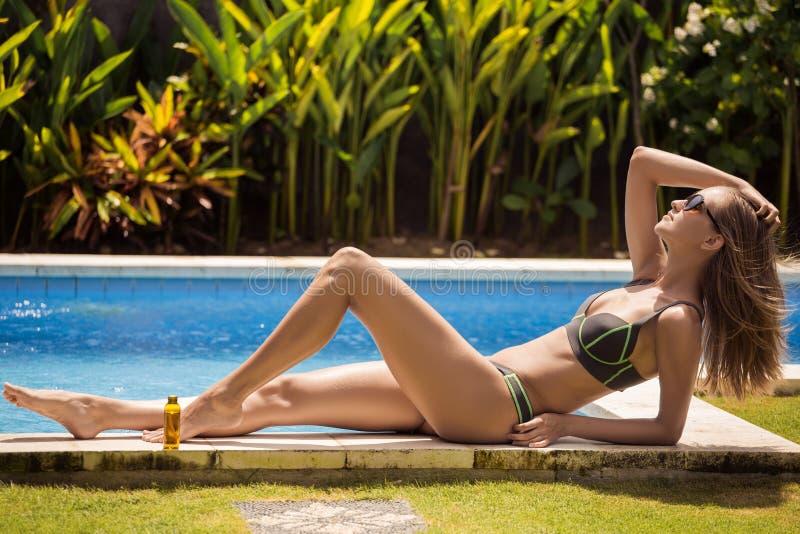 Mujer hermosa delgada joven en tomar el sol del bikini imagen de archivo