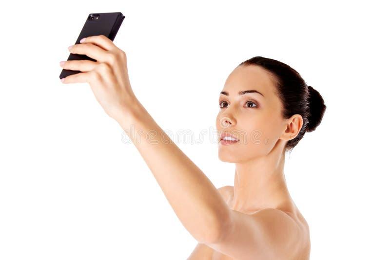 Mujer hermosa desnuda que toma el selfie en el fondo blanco imagenes de archivo