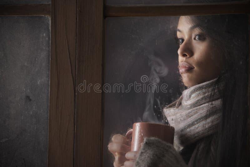 Mujer hermosa detrás de la ventana con una taza de café fotografía de archivo libre de regalías