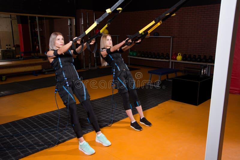 Mujer hermosa dos en el traje muscular eléctrico del estímulo que hace el ejercicio agazapado para la parte posterior y con la su fotos de archivo