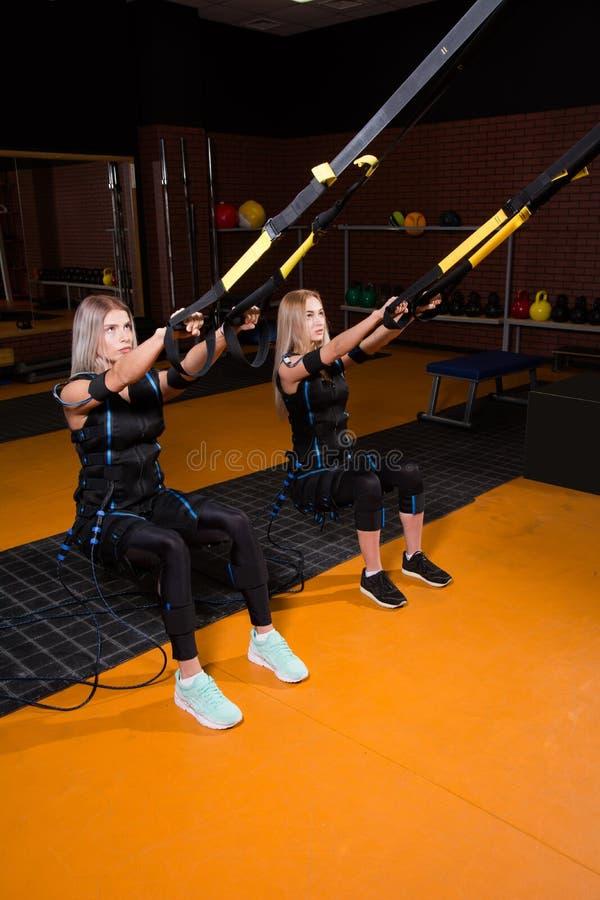 Mujer hermosa dos en el traje muscular eléctrico del estímulo que hace el ejercicio agazapado para la parte posterior y con la su foto de archivo