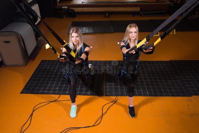 Mujer hermosa dos en el traje muscular eléctrico del estímulo que hace el ejercicio agazapado para la parte posterior y con la su imagen de archivo libre de regalías