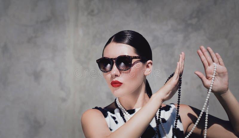 Mujer hermosa elegante con las gafas de sol, los collares de la perla y los labios pintados brillantes imagen de archivo