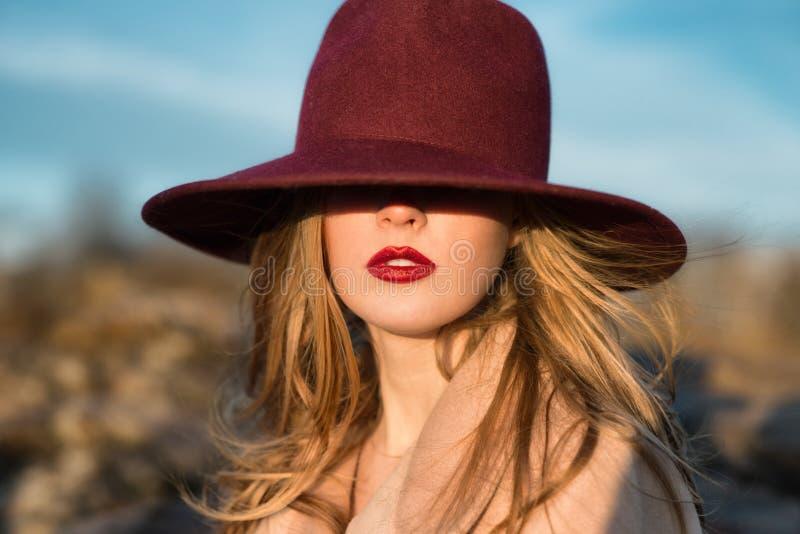 Mujer hermosa elegante con los labios y el sombrero rojos imagenes de archivo