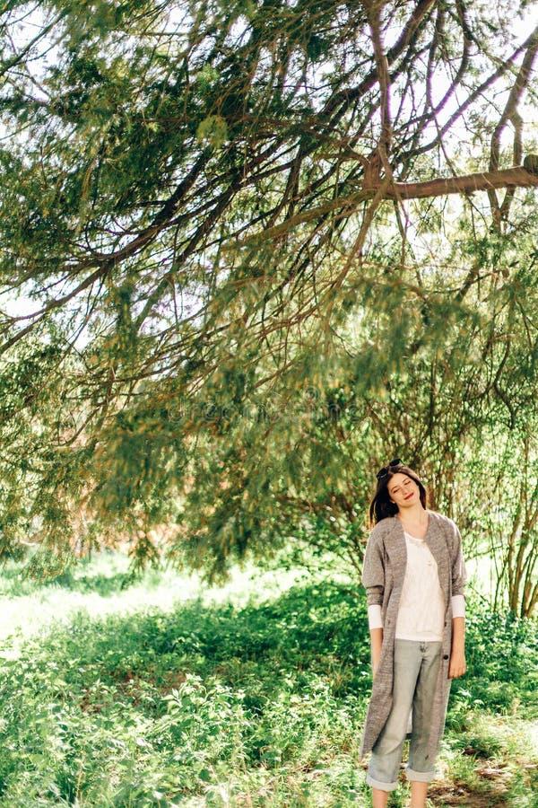 Mujer hermosa elegante del inconformista que se relaja bajo ramas verdes adentro fotografía de archivo