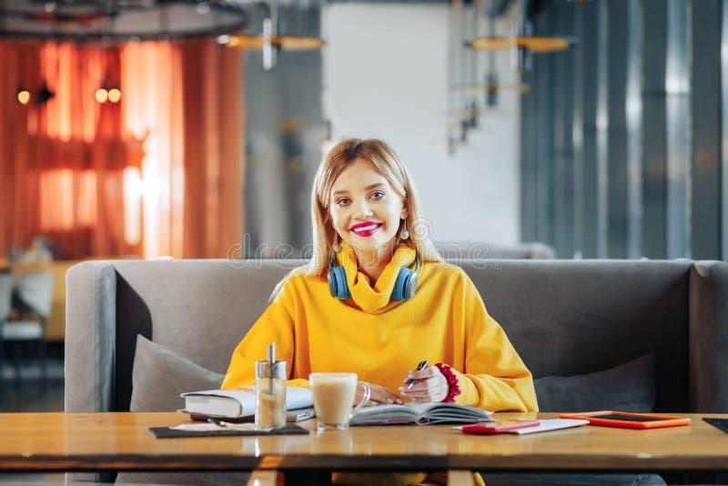 Mujer hermosa elegante que siente alegre mientras que trabaja en cafetería fotografía de archivo