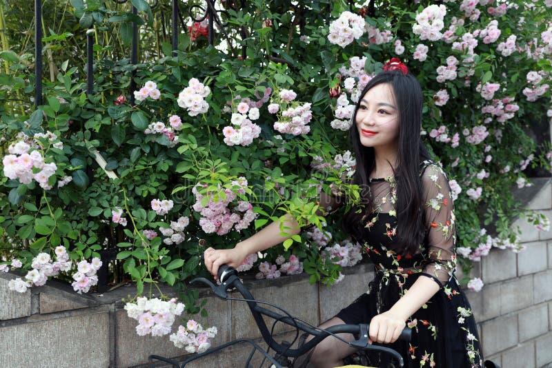 Mujer hermosa, elegante vestida joven con la bicicleta Sano, completando un ciclo foto de archivo
