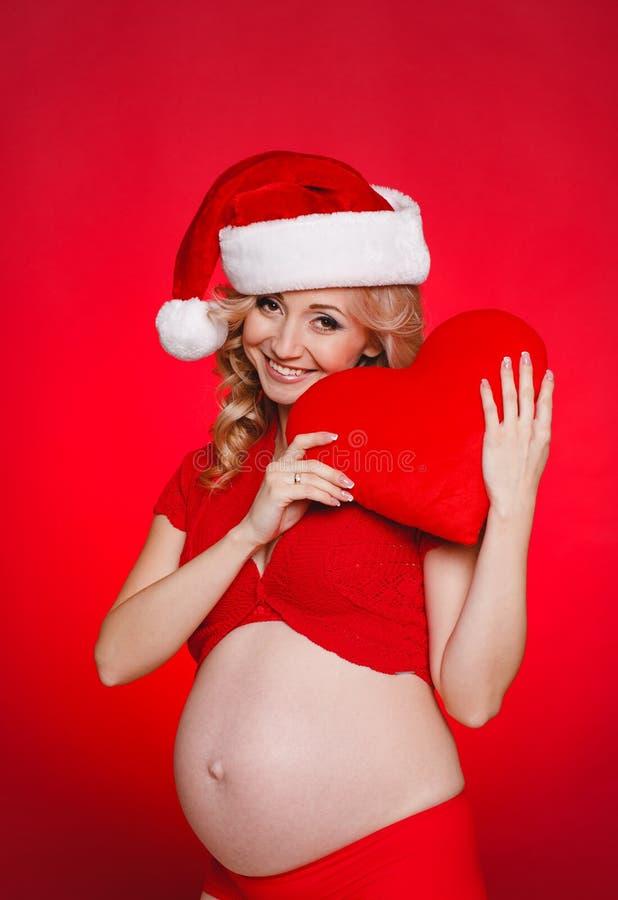 Mujer hermosa embarazada que sostiene la almohada roja del corazón en sus manos aisladas en fondo rojo fotos de archivo libres de regalías