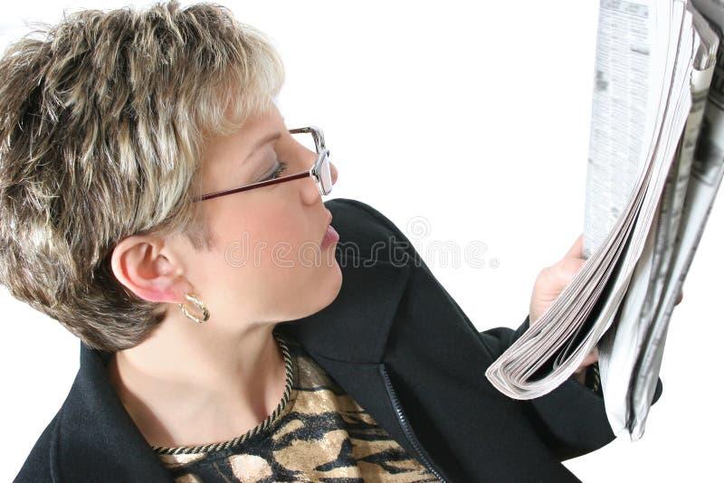 Mujer hermosa en años 30 que lee el periódico sobre blanco fotografía de archivo libre de regalías