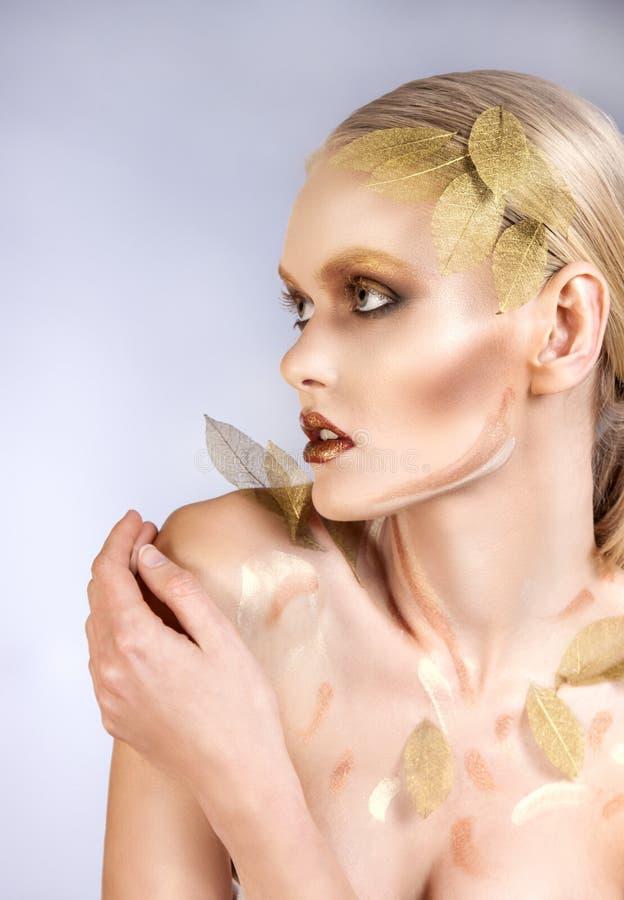 Mujer hermosa en accesorios con las hojas del oro fotos de archivo libres de regalías