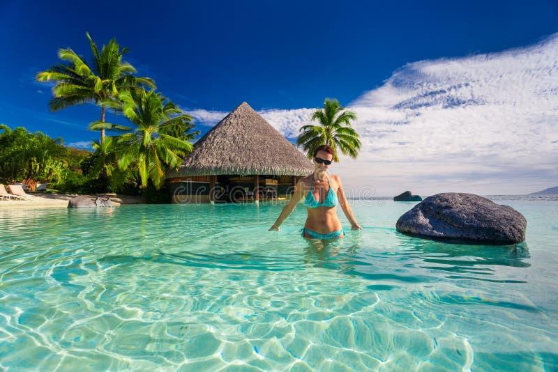 Mujer hermosa en bikini azul dentro de la piscina tropical del infinito, TA fotografía de archivo