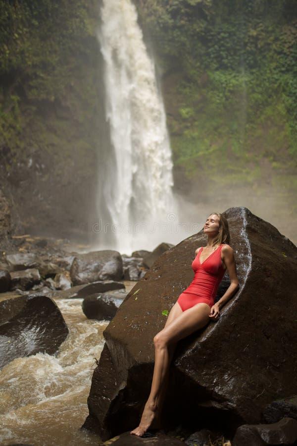 Mujer hermosa en bikini y cascada rojos imagen de archivo